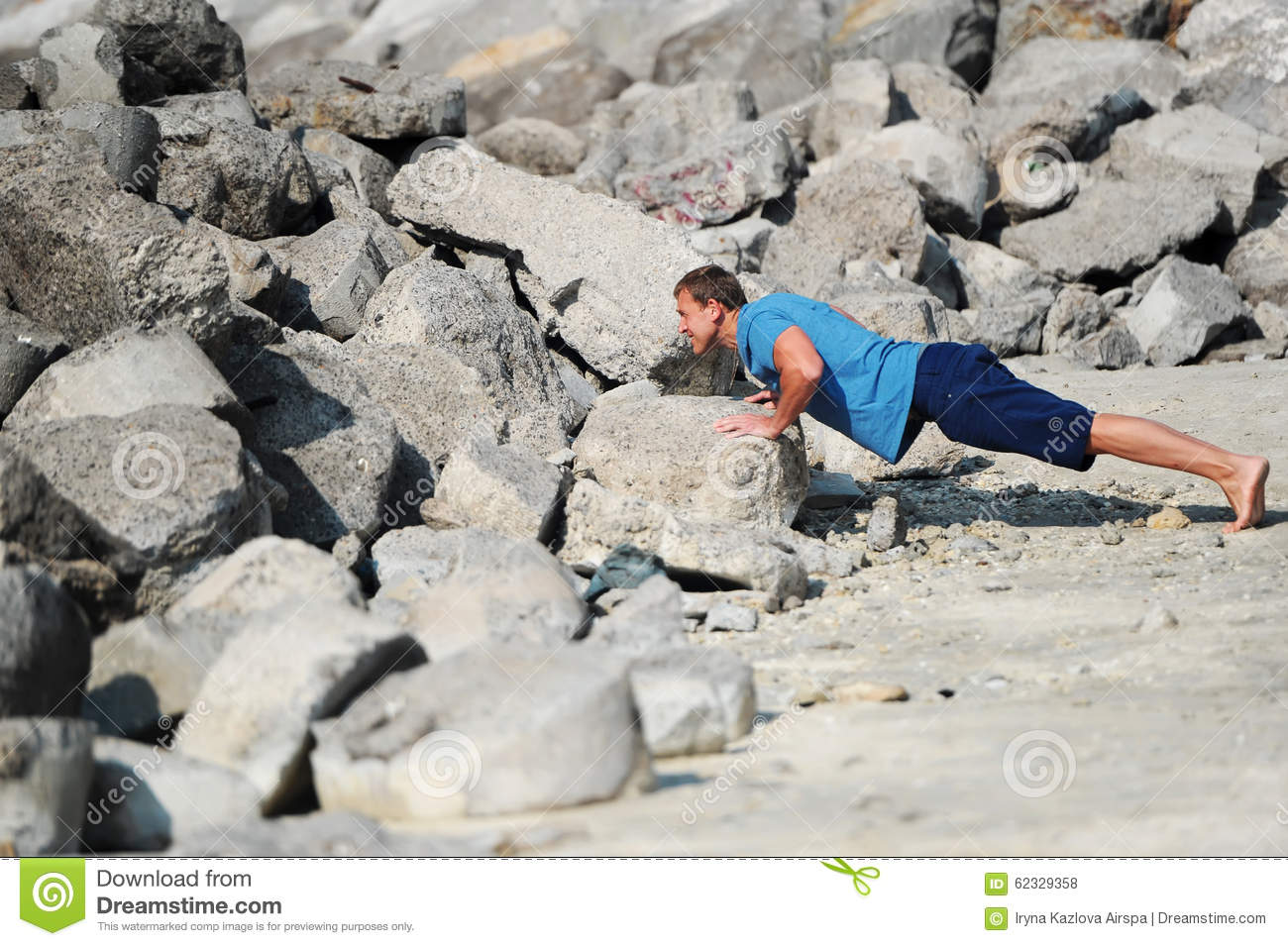 The young man carries out push-ups among stones