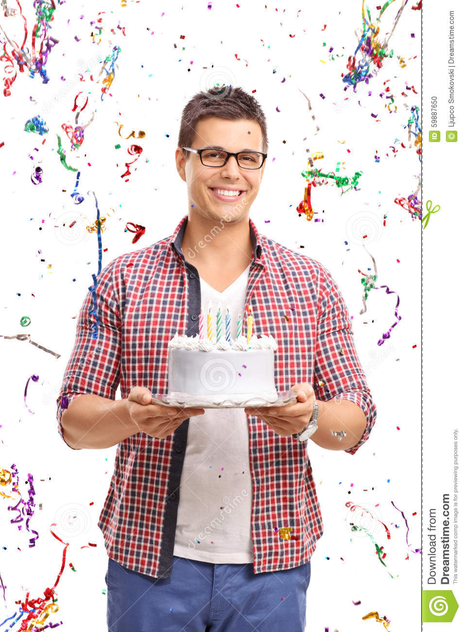 Young man carrying a birthday cake