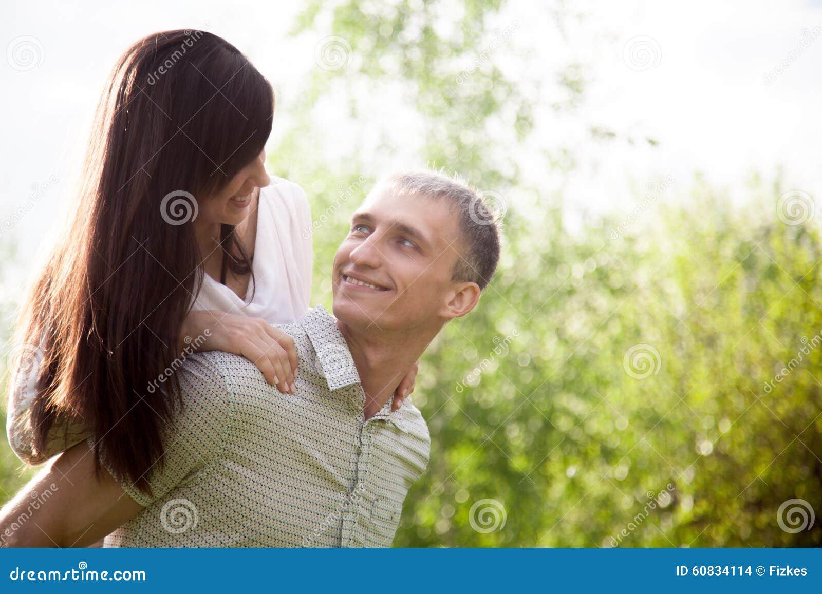 Young man carrying piggyback his girlfriend