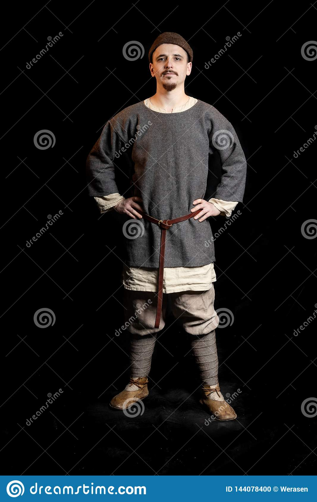 young man in casual gray clothes and a hat of the Viking Age looks serious, hands on hips