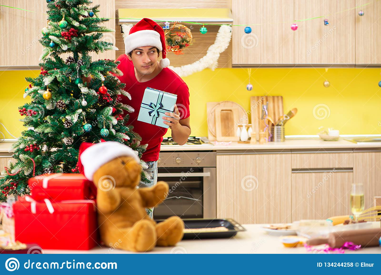 The young man celebrating christmas in kitchen