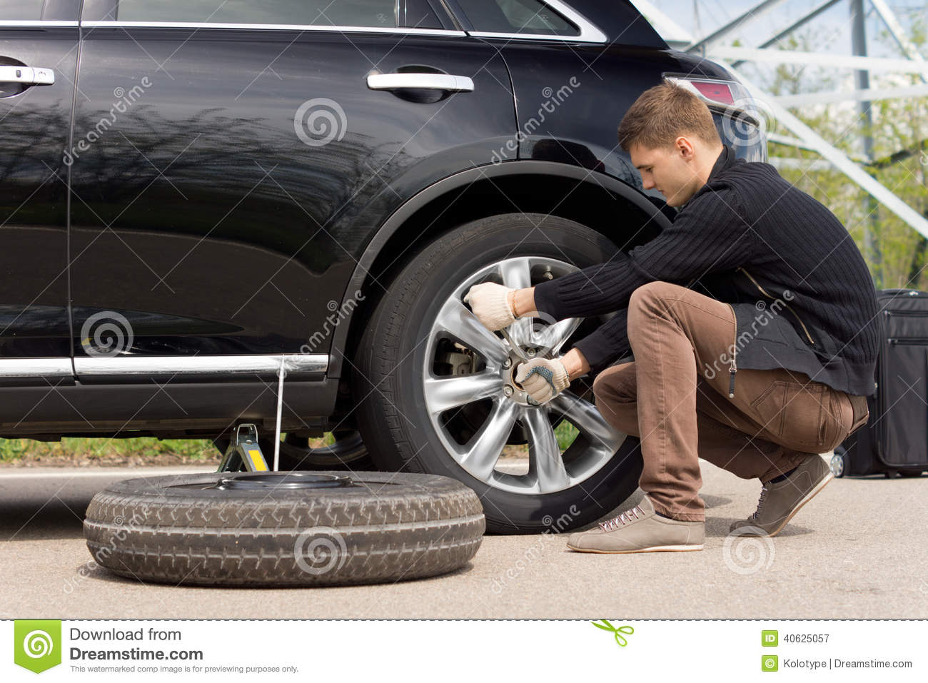 Young Man Changing The Punctured Tyre On His Car Stock