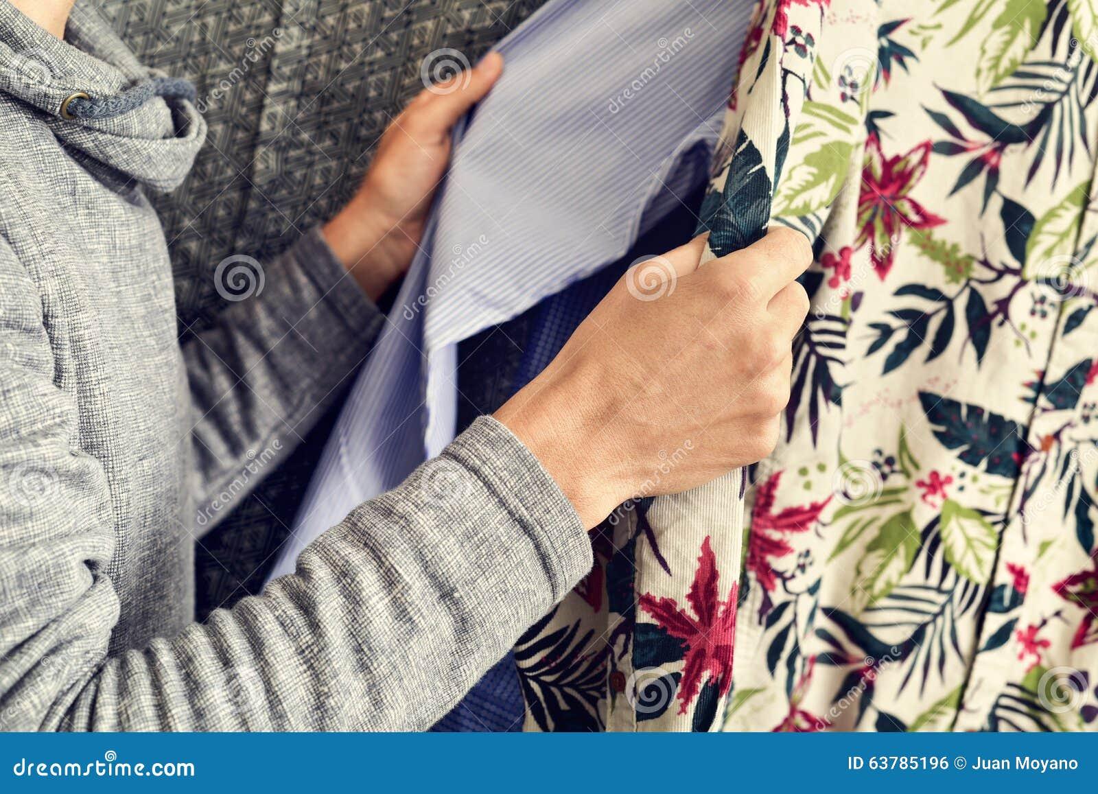 Young man choosing a shirt