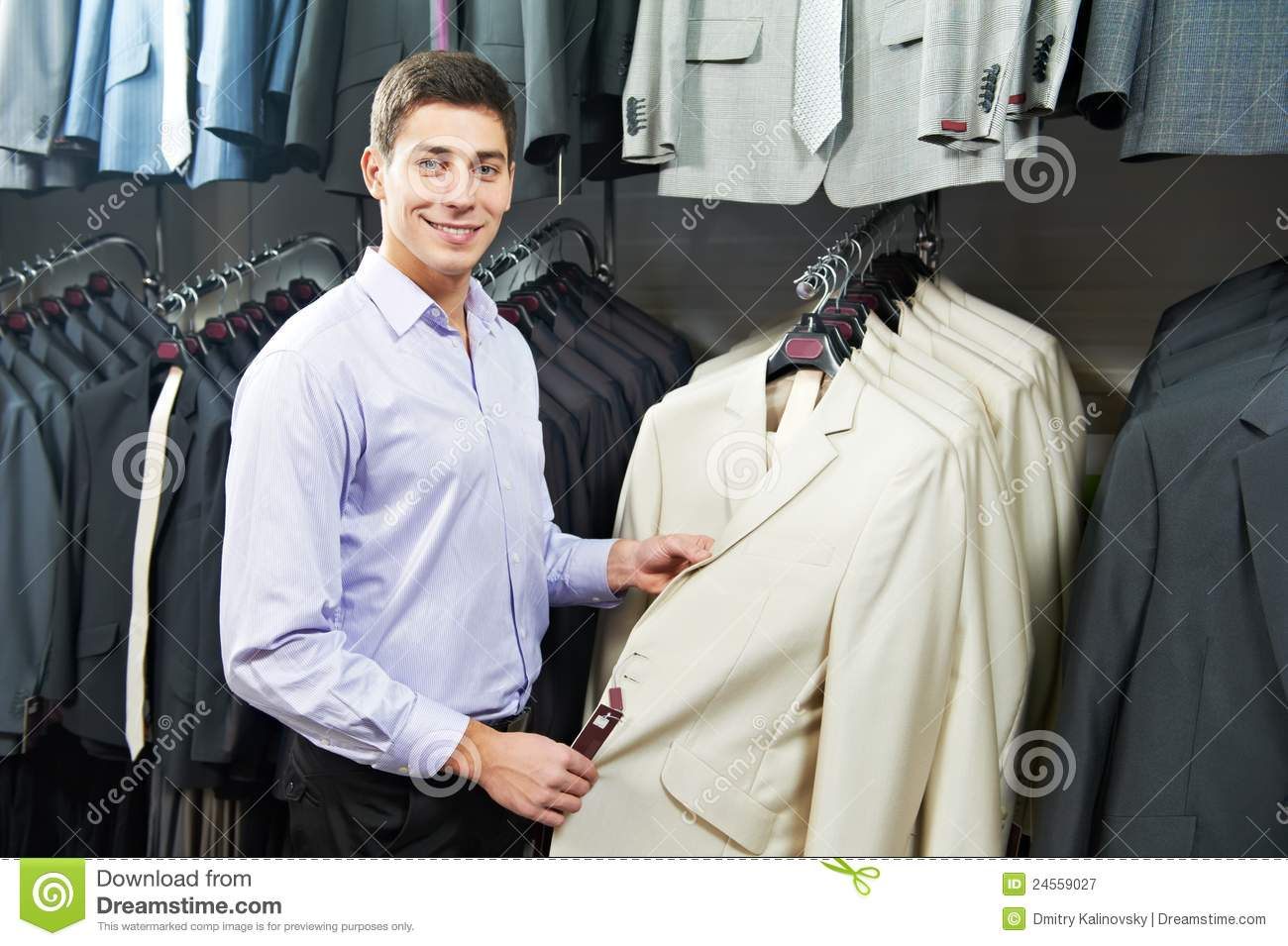 57022976 Young man choosing suit jacket during apparel shopping at clothing store