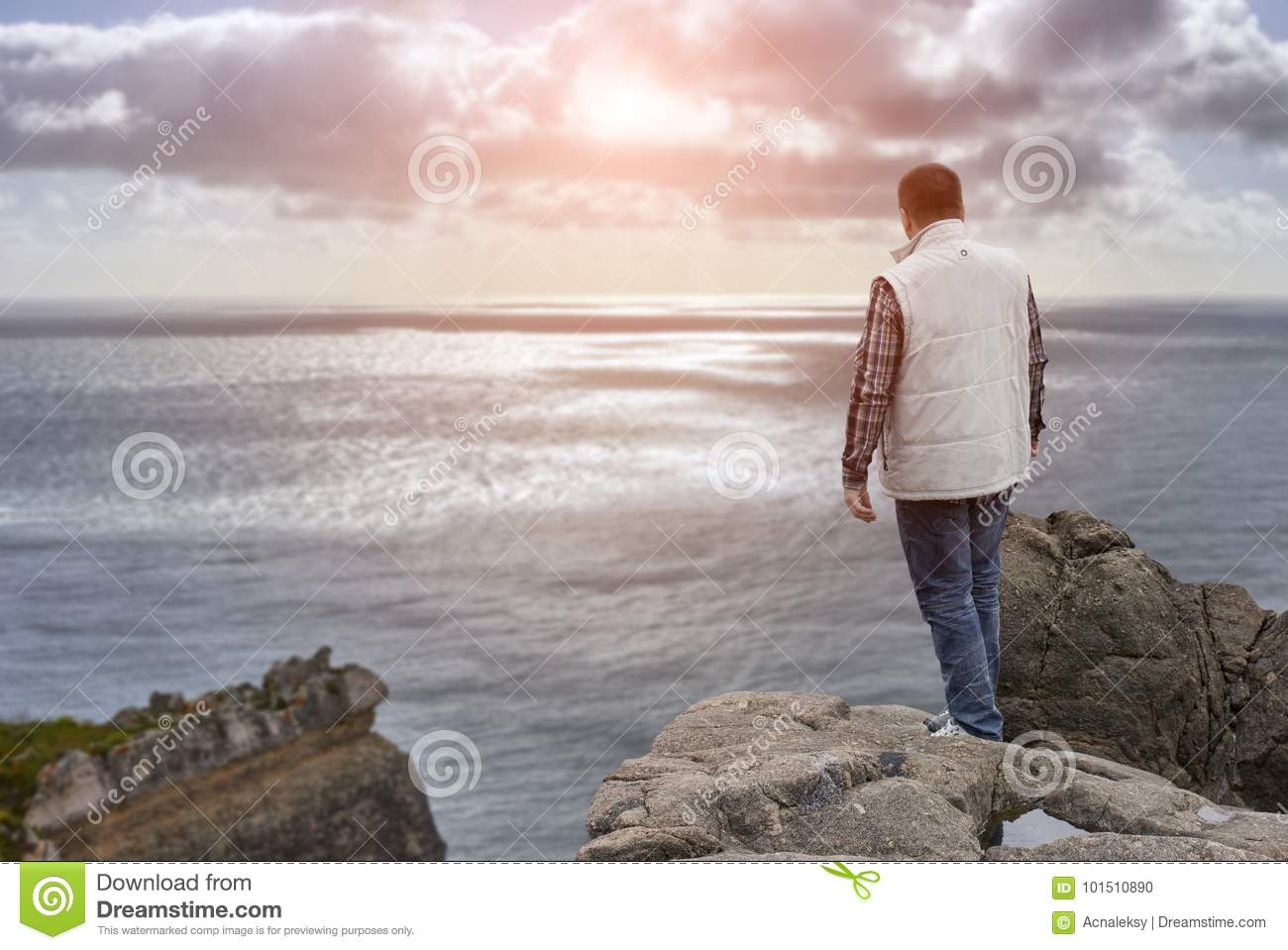 Young man on cliff`s edge at sunset