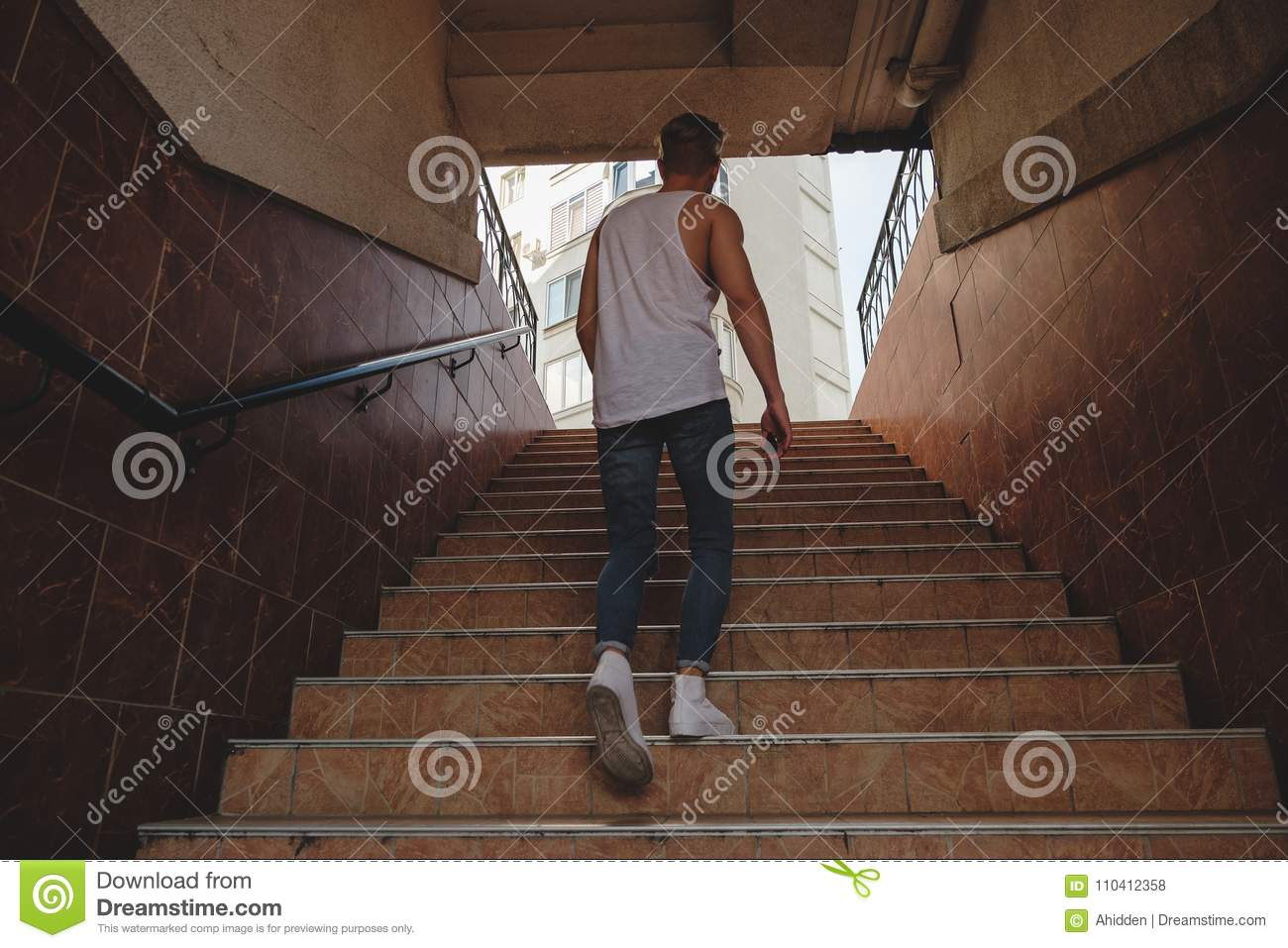 Download Young Man Climbing Stairs In Pedestrian Subway Stock Photo - Image of support, walk: 110412358
