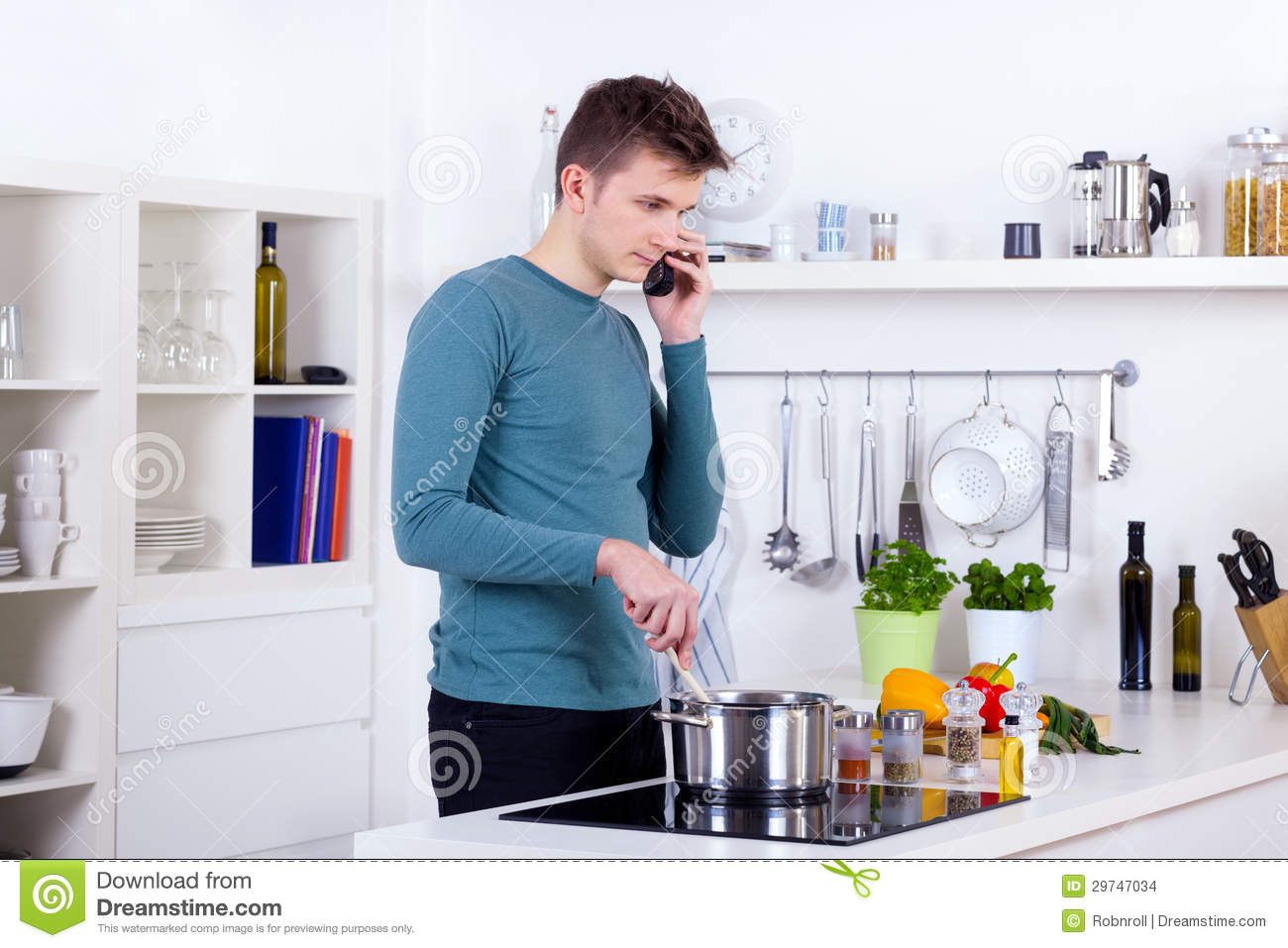 Young Man Cooking A Meal And Talking On The Phone In The Kitchen ...
