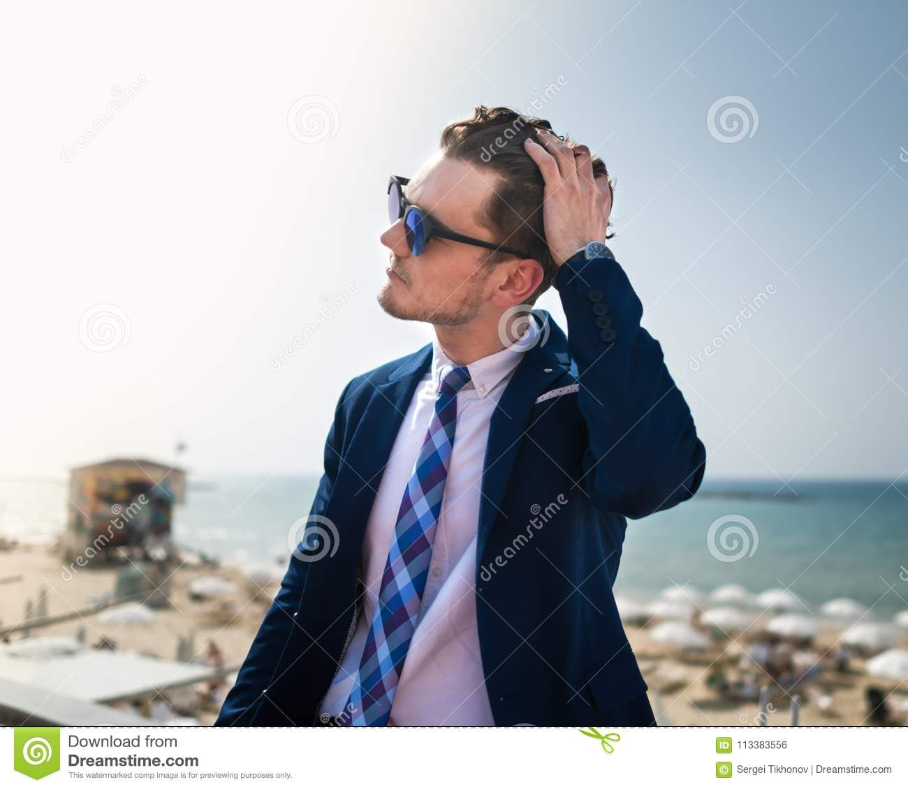 Young man corrects his hair on the background of the sea and sky