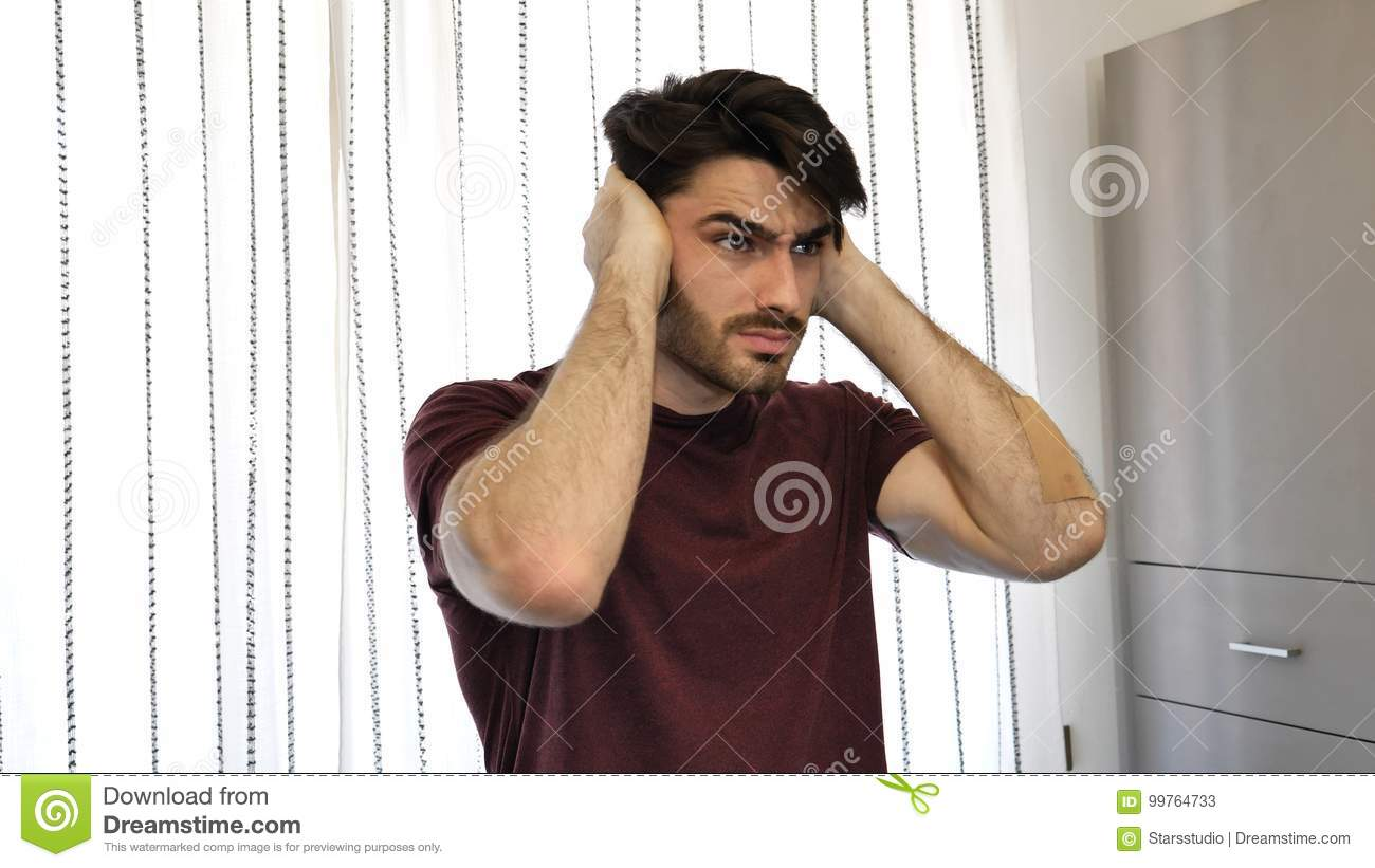 Young man covering his ears, too much noise