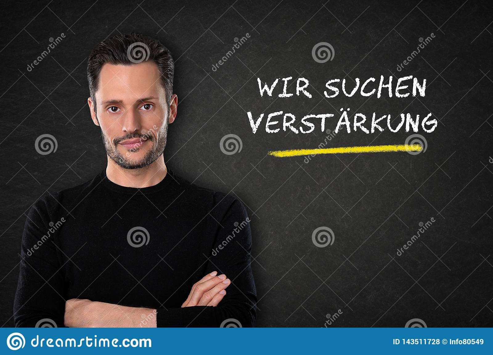 Young man with crossed arms and `Wir suchen dich` text on a blackboard background. Translation: `We are looking for you`