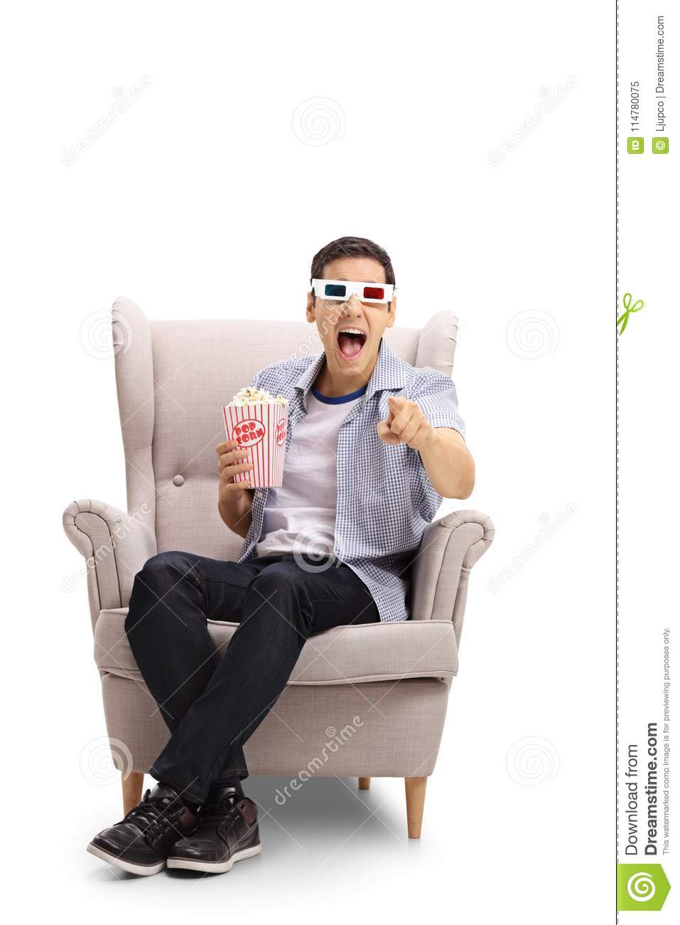 Young man with 3D glasses and popcorn seated in an armchair laughing and pointing at the camera