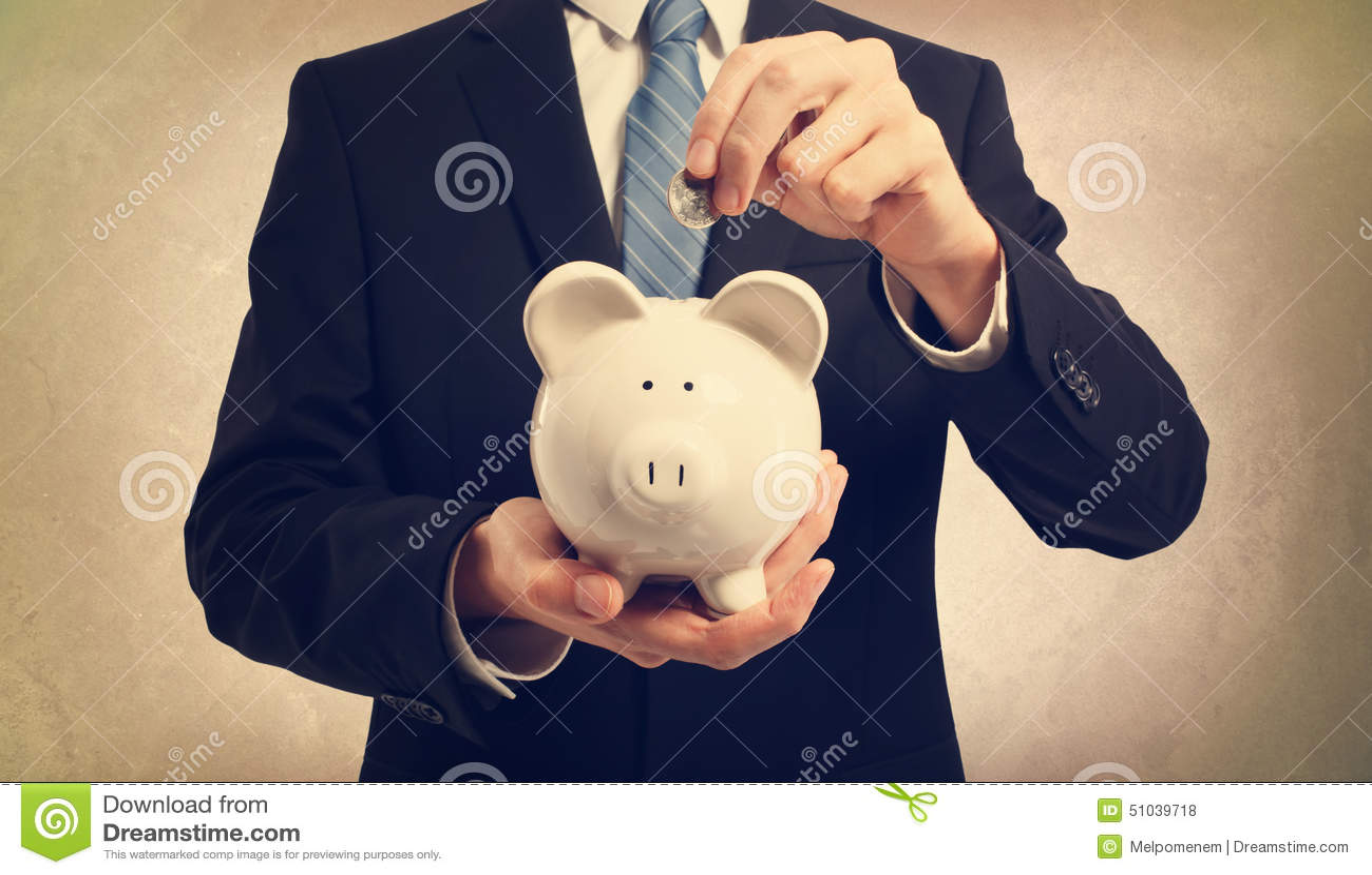 Young man depositing money in piggy bank