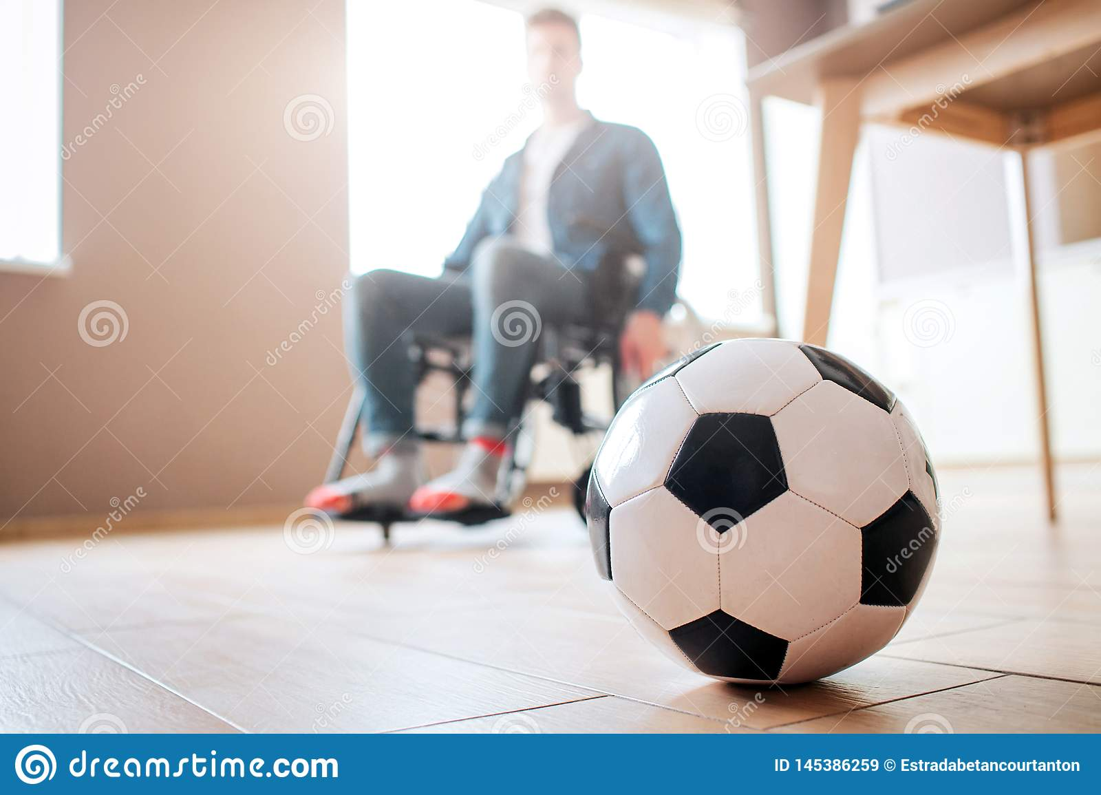 Young man with disability sitting on wheelchair and look down at ball for game. Ex sportsman. Upset and unhappy. Trauma