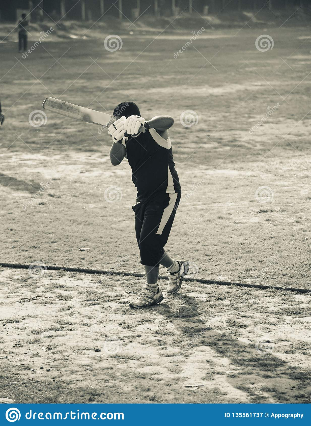 Young man is doing batting practice in a field