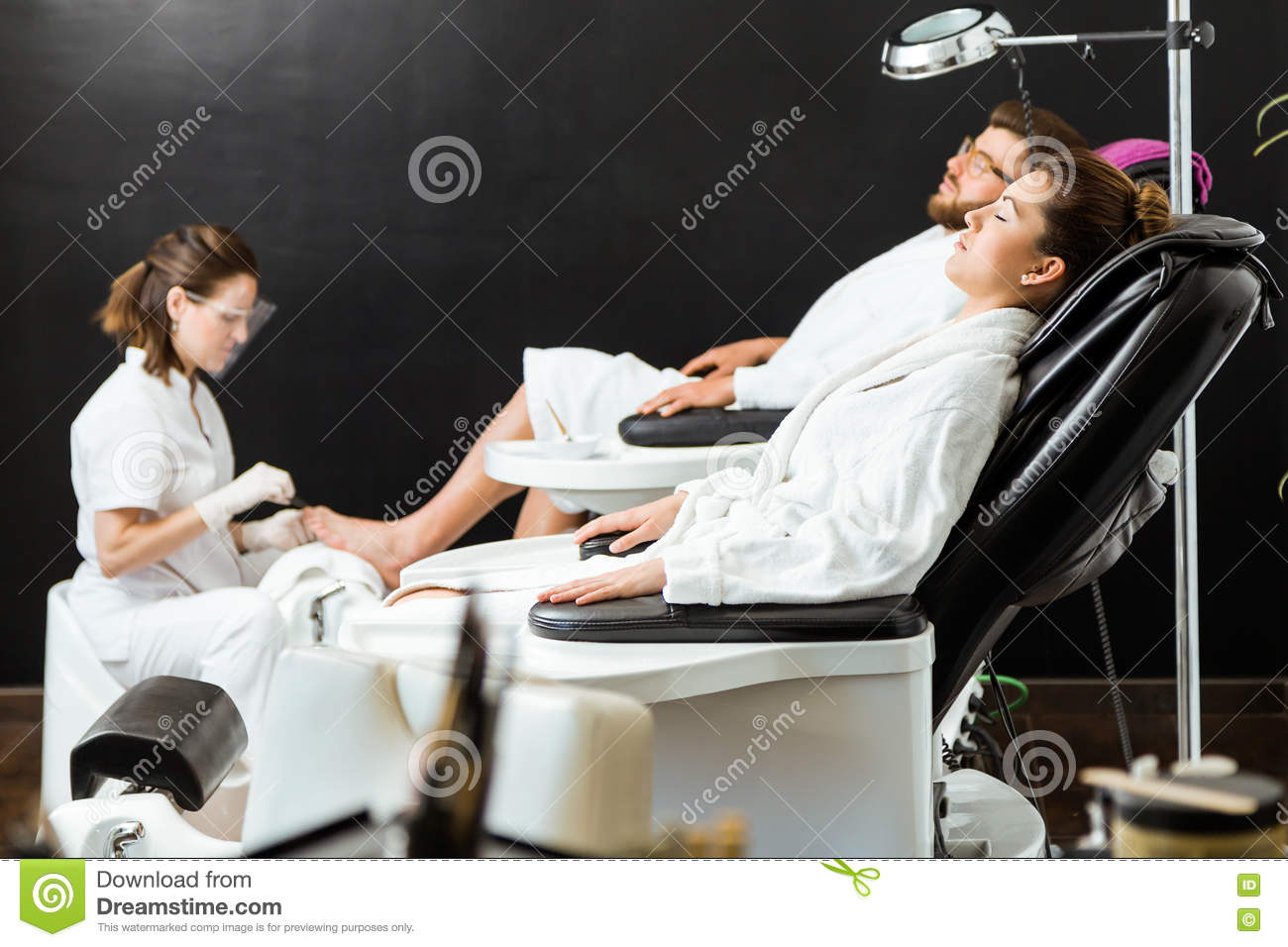 Young man doing pedicure in salon beauty concept stock for Salon younga