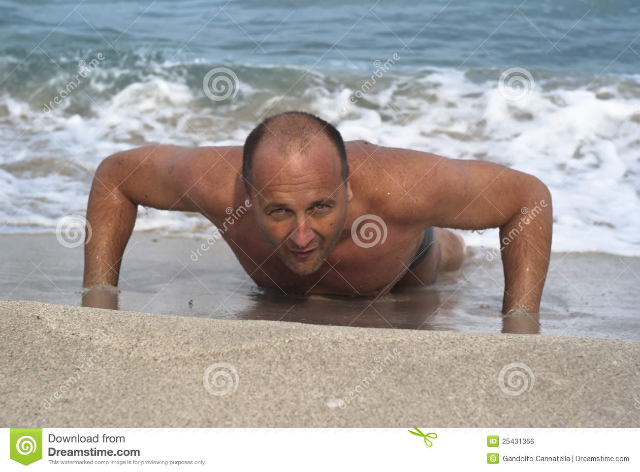 Young man doing pushups on the beach