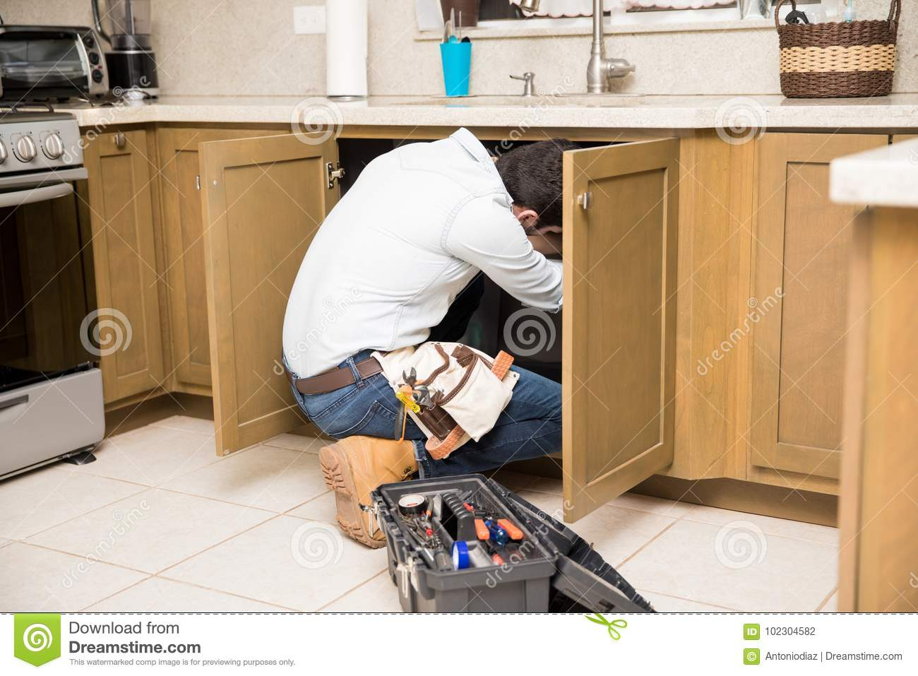 Plumber Getting Inside A Kitchen Cabinet Stock Photo Image Of