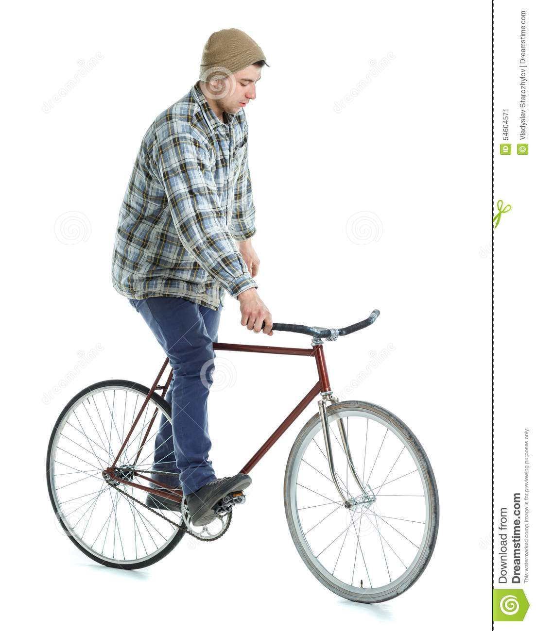 Young man doing tricks on fixed gear bicycle on a white