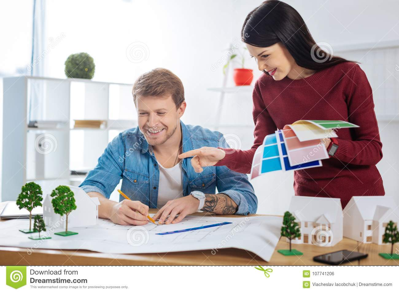 Young man drawing while his colleague holding color palettes
