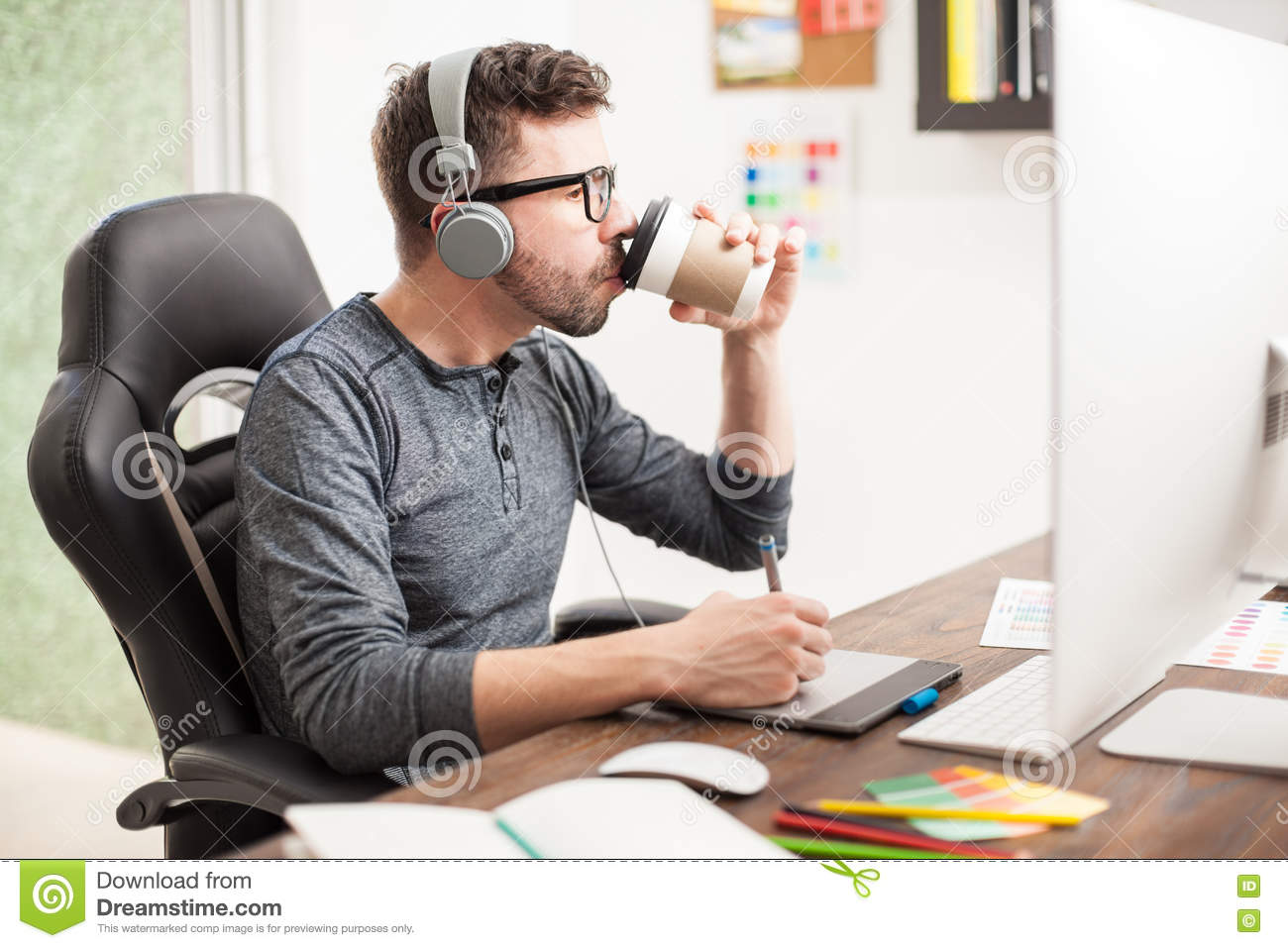 Coffee At Work ~ Young man drinking coffee at work stock photo image of