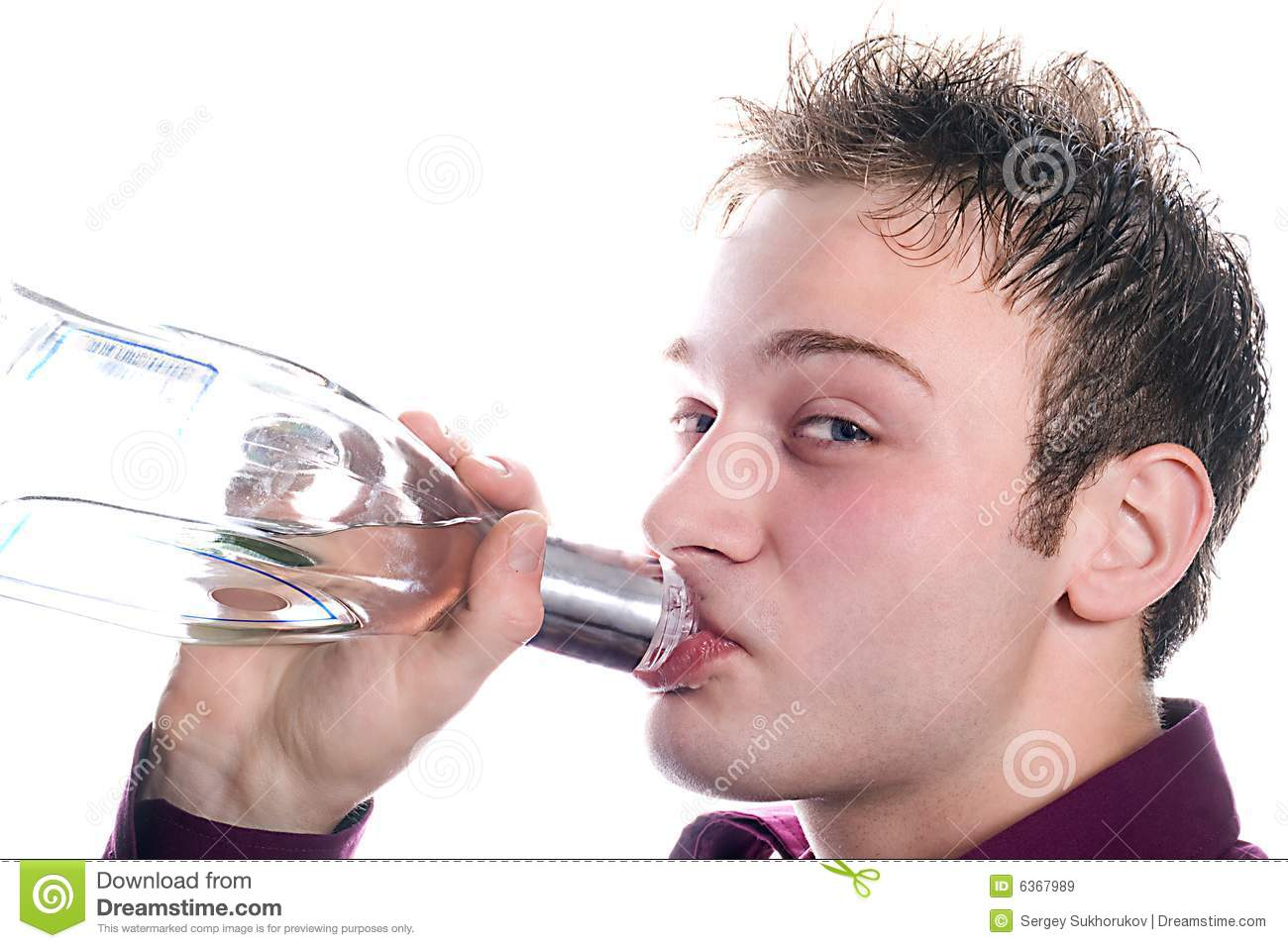The young man drinks vodka from a bottle