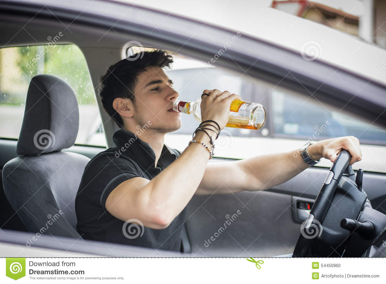 Young man driving his car while drinking alcohol