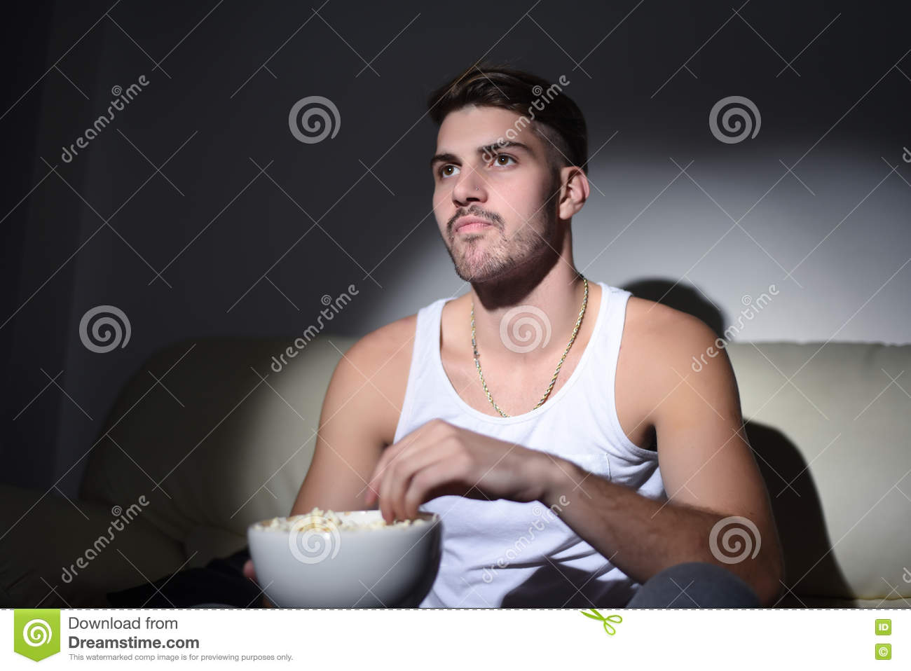 young man eating popcorn and watching movies stock image image of