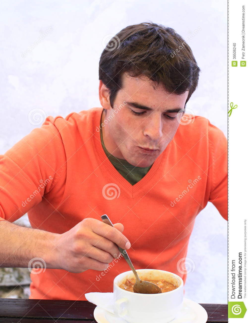 Young man eating sup