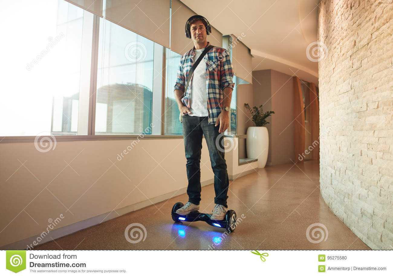 Young man on an electrical self-balancing scooter in office