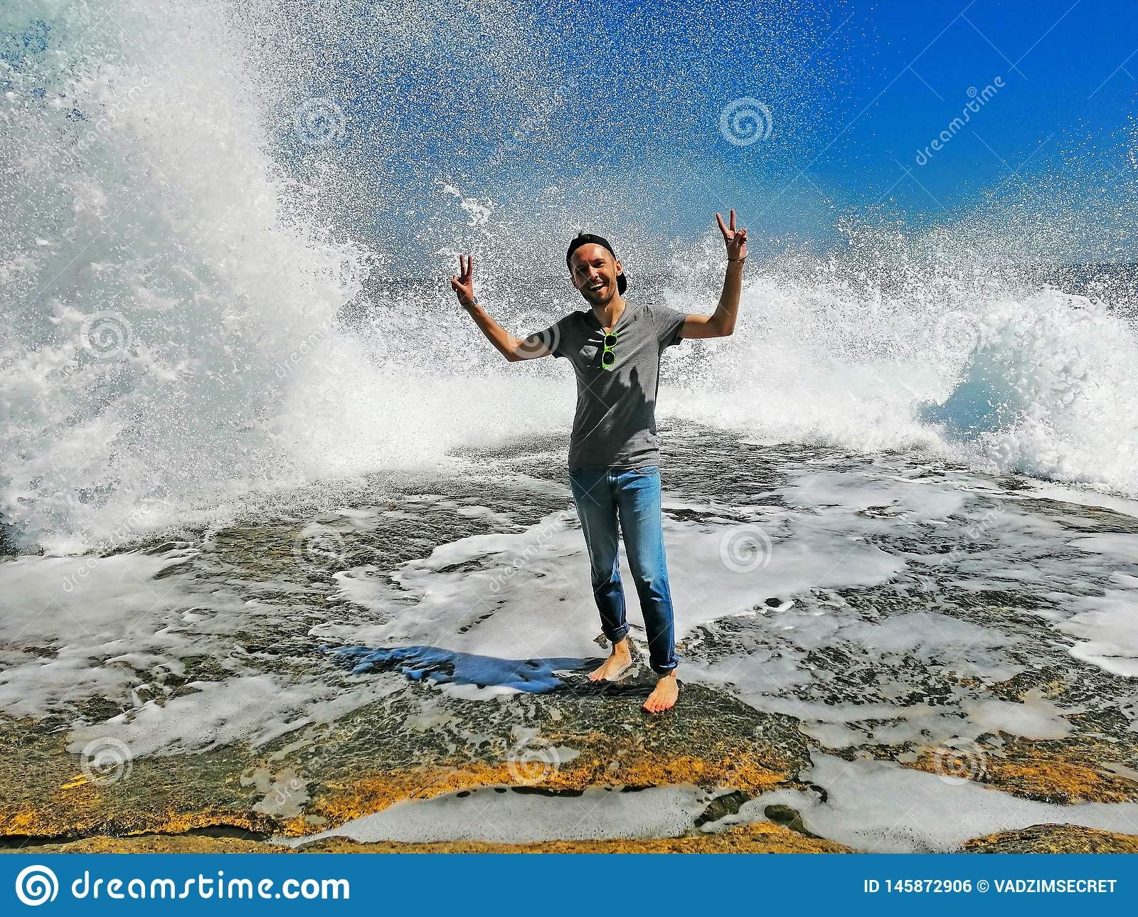Young man enjoying high waves with water waves with splashes