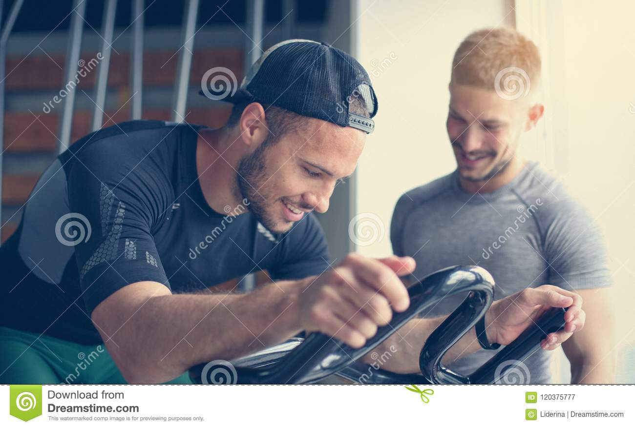 Young man exercise on stationary bikes in fitness class.