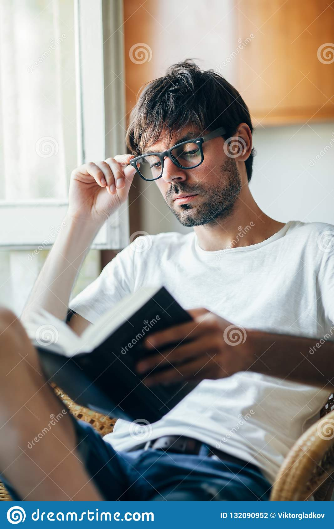 1750508afda Young handsome man in eyeglasses reading book sitting on chair at home