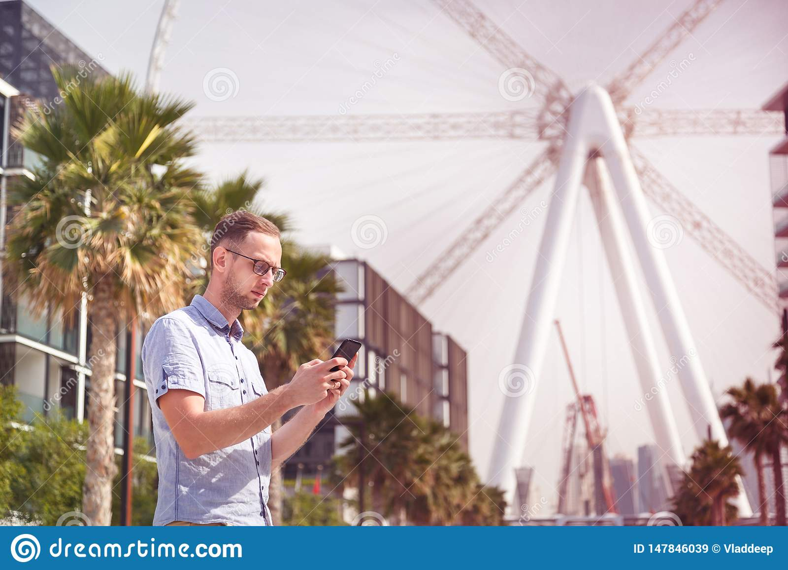 Young man in eyeglasses using his phone in Dubai
