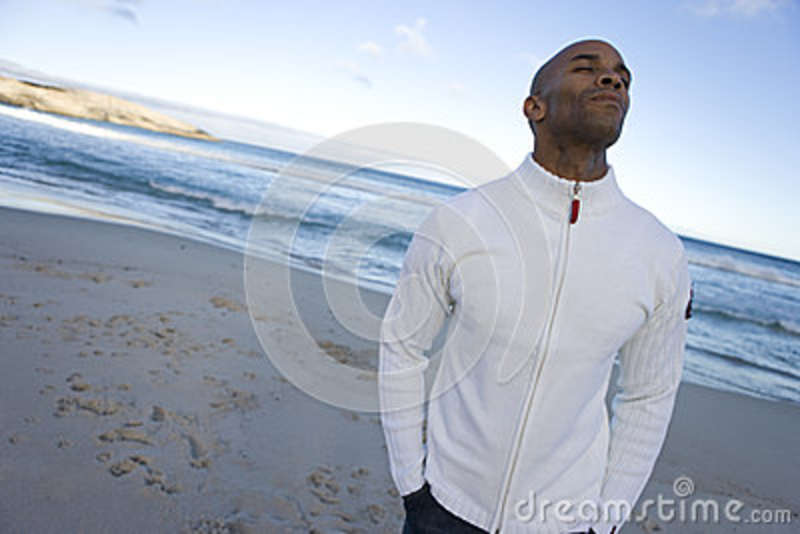 Young man with eyes closed on beach, hands in pockets