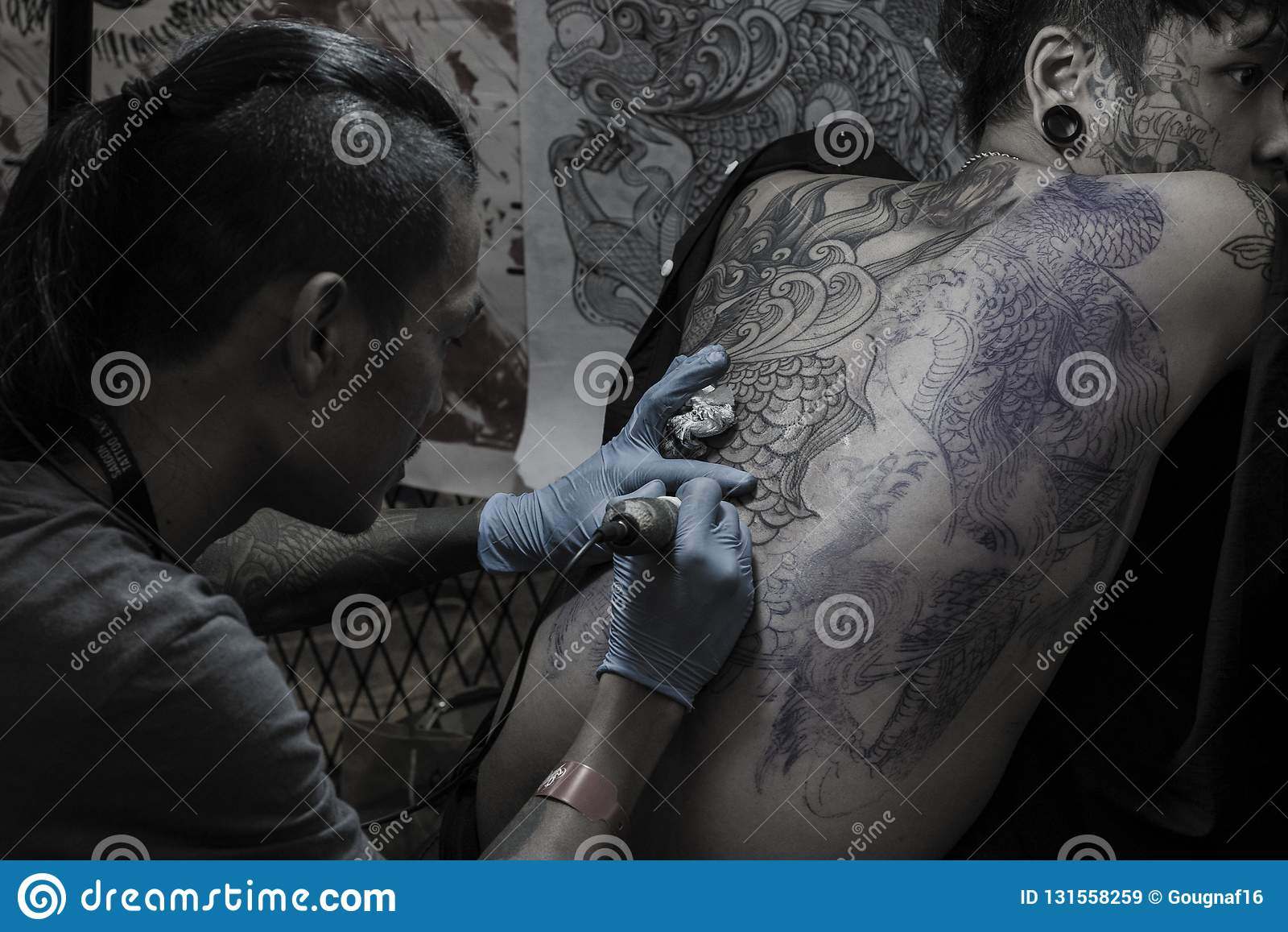 Young Man With A Face Tattoo Is Getting A Full Back Tattoo By Black