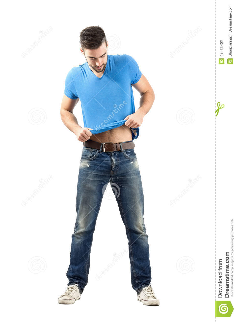 Young Man Fashion Model Putting On His T-shirt Stock Photo