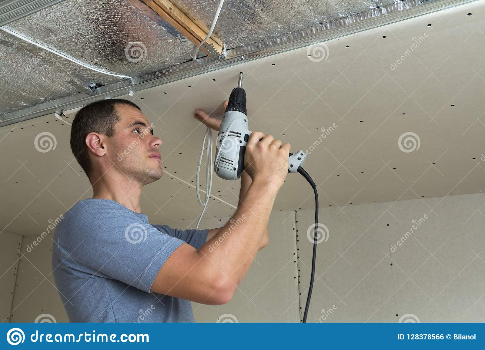 Young Man Fixing Drywall Suspended Ceiling To Metal Frame Using Pics Photos Do It Yourself Electrician Electrical Screwdriver
