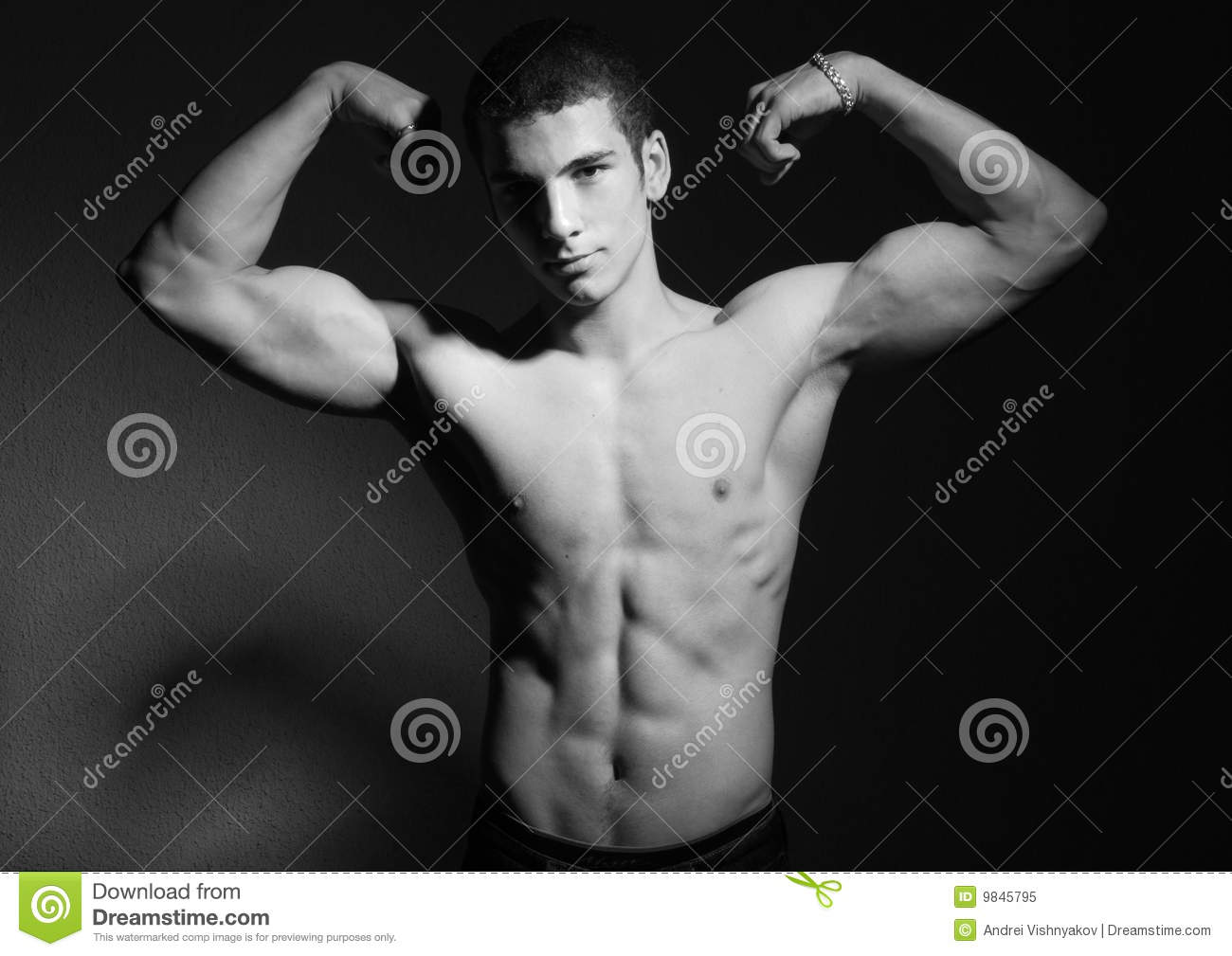 ... chested young man flexing muscles, black and white studio background