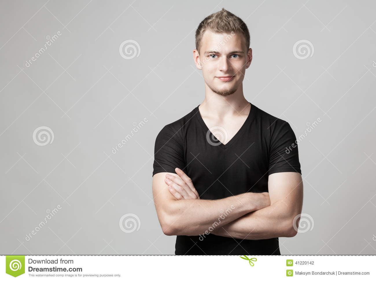 Young man with folded arms isolated on light background