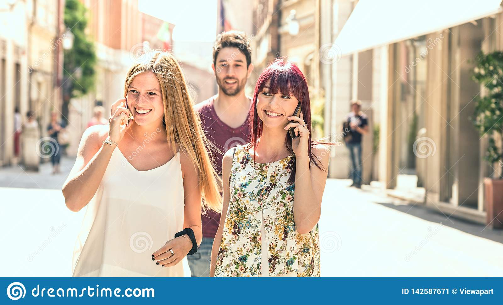 Young man following pretty women while having fun together on city street - Technology concept in everyday lifestyle