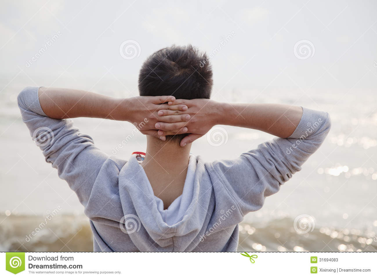 Young Man With Hands Behind Head, Looking Out To Sea Stock Photos Image 31694083