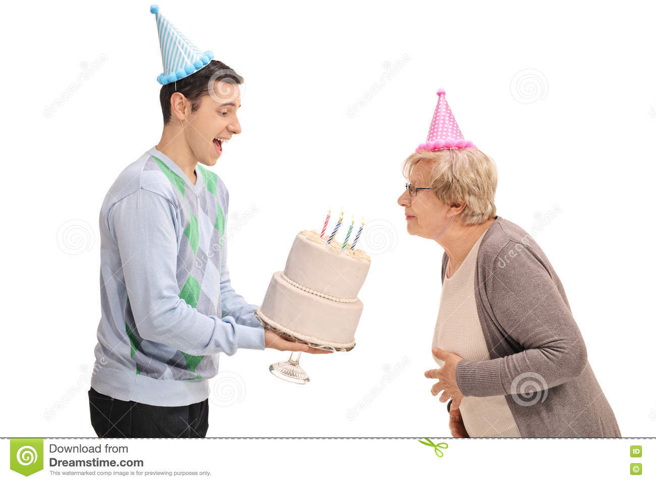Young man holding a birthday cake with a mature woman blowing th