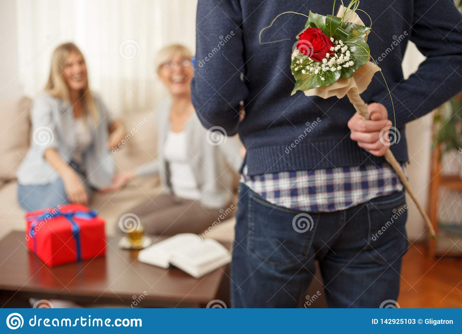 Young man holding bouquet of flowers behind the back for his mother