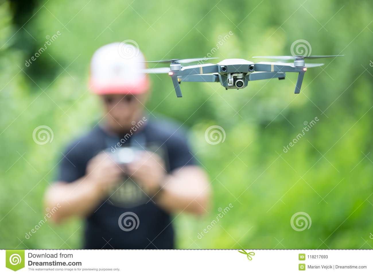 Young man holding remote controller and flying with drone in the