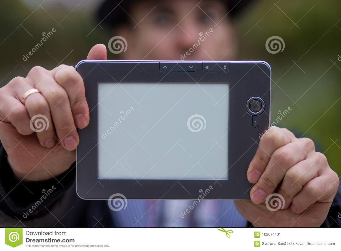 A young man holds a digital tablet in front of him