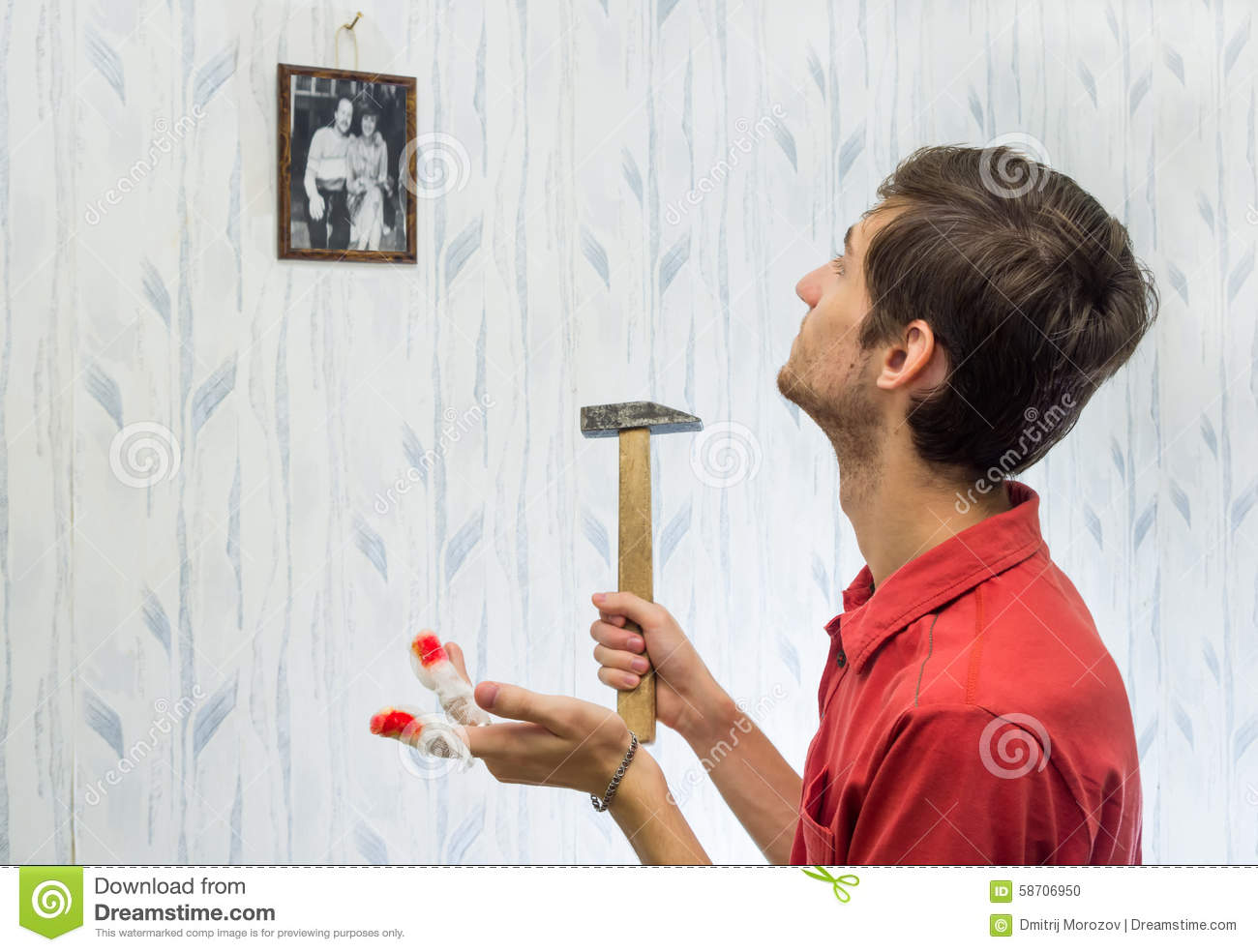 The young man hung pictures on the wall, improving interior