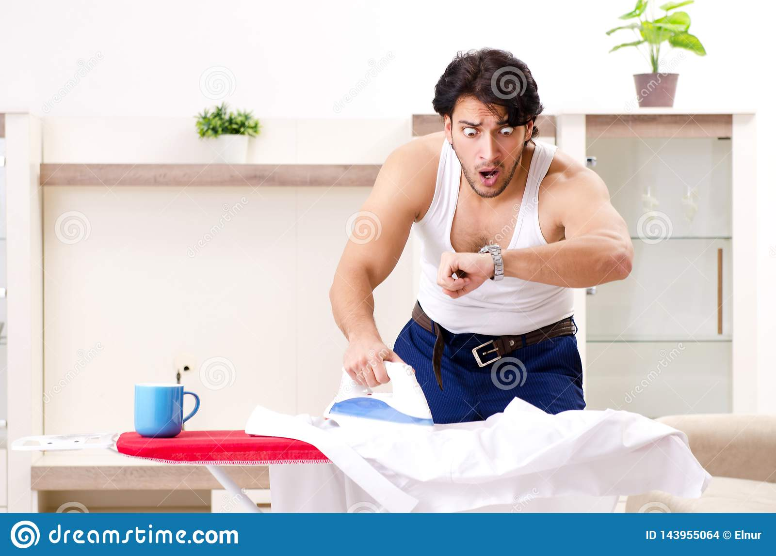Ams Nude the young man ironing in the bedroom stock photo - image of