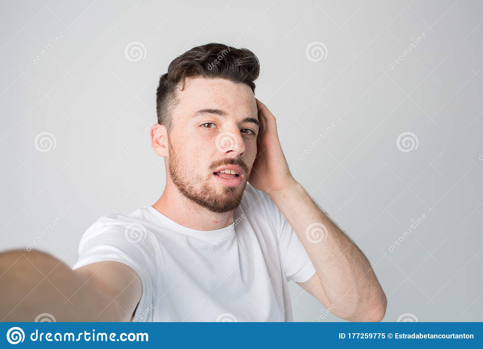 Young Man Isolated Over Background Guy Hold Camera And Take Selfie Posing Alone With Pleasure Hold One Hand On Ear Stock Image Image Of Modern Beautiful 177259775