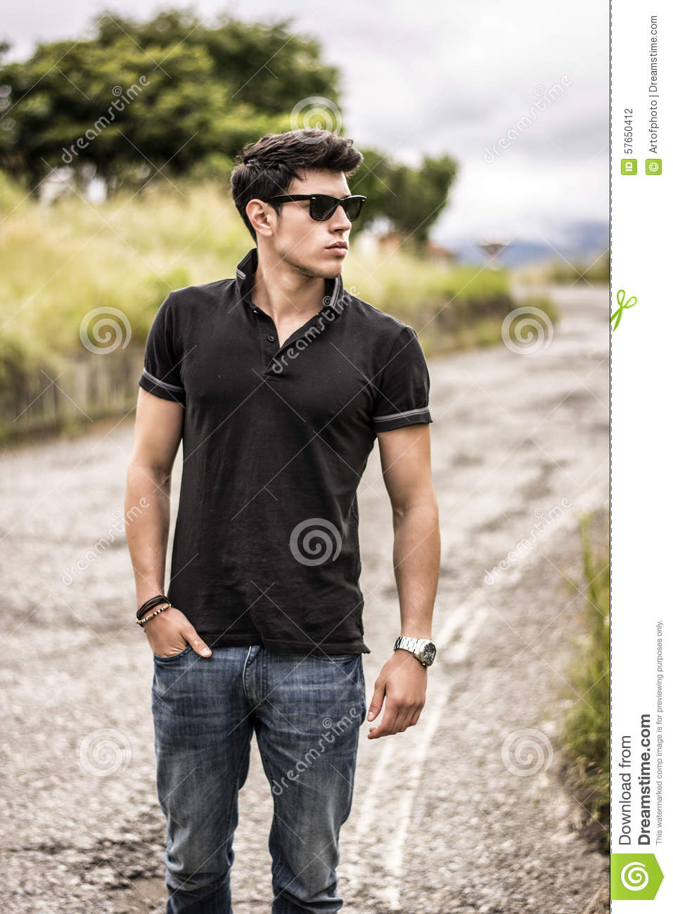Black t shirt and jeans - Young Man In Jeans And Black T Shirt Walking Along Stock Photo