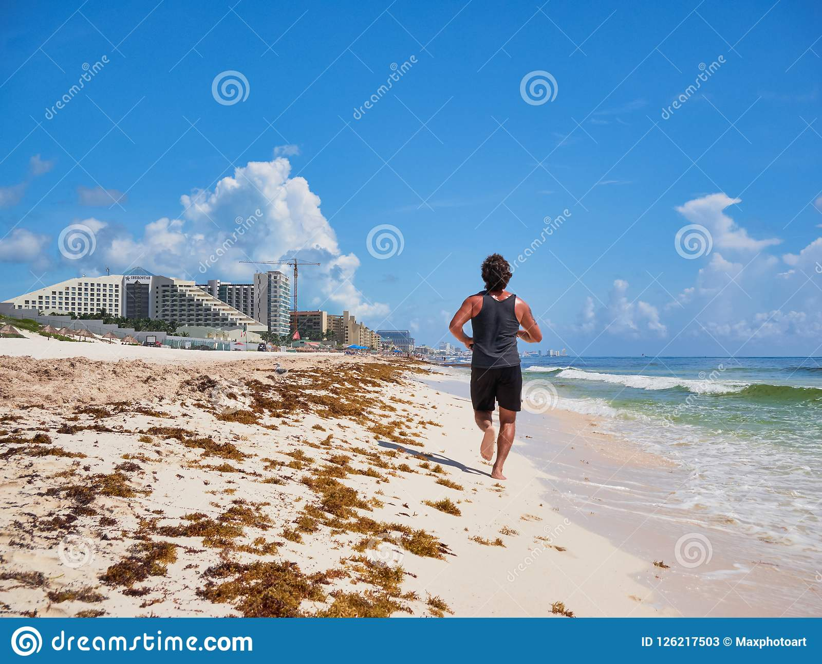 Young man jogging in tropical beach